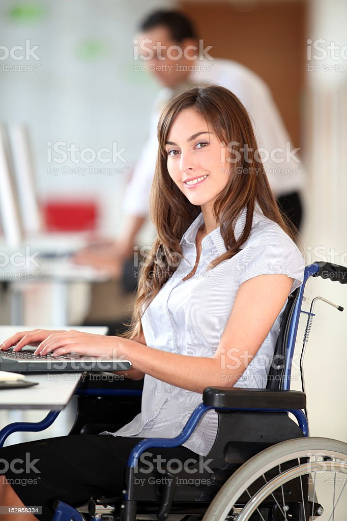 Handicapped businesswoman working on a laptop at work stock photo