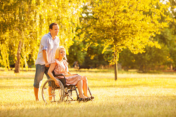 Handicapped Couple Outdoors. Portrait of an young couple, man and disabled woman in wheelchair walking in a park. long hair stock pictures, royalty-free photos & images