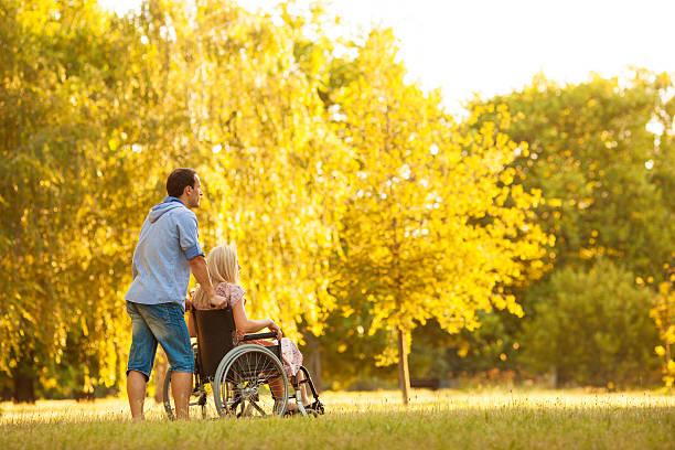 handicapped couple outdoors. - lang haar stockfoto's en -beelden