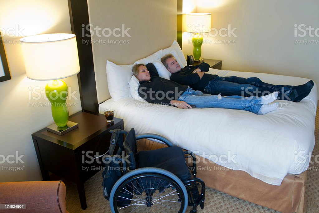 Handicapped Couple Relaxing on Hotel Bed royalty-free stock photo