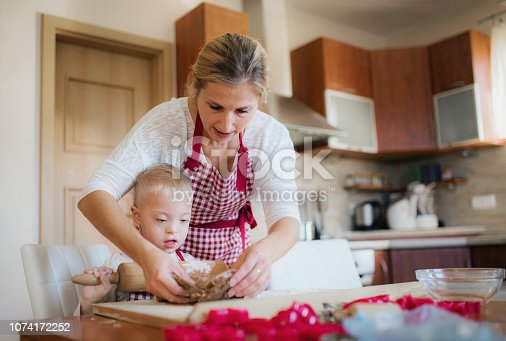 istock A handicapped down syndrome boy with his mother indoors baking. 1074172252