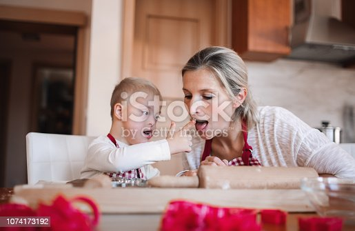 istock A handicapped down syndrome boy with his mother indoors baking. 1074173192