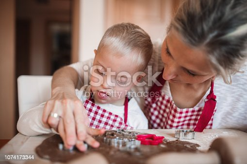 istock A handicapped down syndrome boy with his mother indoors baking. 1074173344