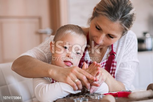 istock A handicapped down syndrome boy with his mother indoors baking. 1074173364