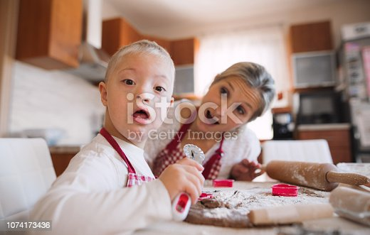 istock A handicapped down syndrome boy with his mother indoors baking. 1074173436