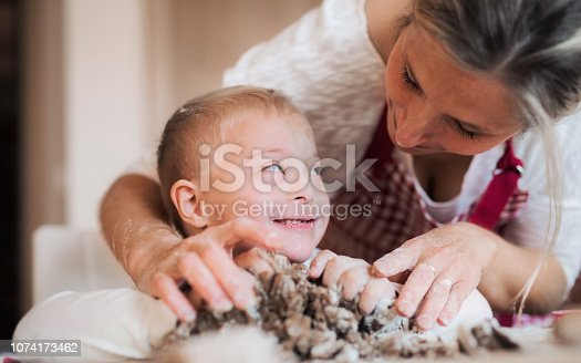 istock A handicapped down syndrome boy with his mother indoors baking. 1074173462