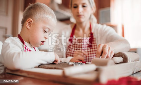 istock A handicapped down syndrome boy with his mother indoors baking. 1074834368