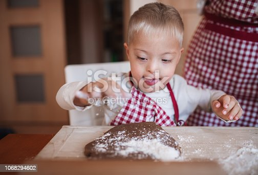 istock A handicapped down syndrome child with his mother indoors baking. 1068294602