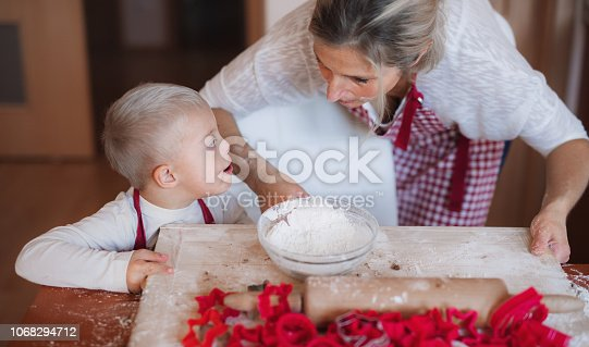 istock A handicapped down syndrome child with his mother indoors baking. 1068294712