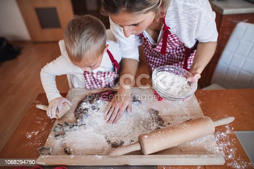istock A handicapped down syndrome child with his mother indoors baking. 1068294750