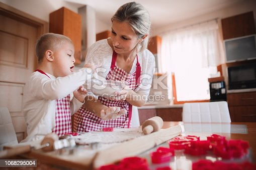 istock A handicapped down syndrome child with his mother indoors baking. 1068295004