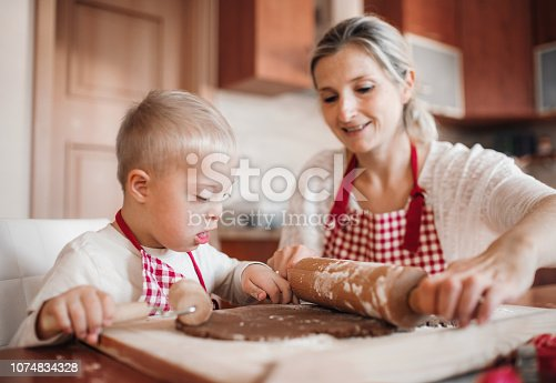 istock A handicapped down syndrome child with his mother indoors baking. 1074834328