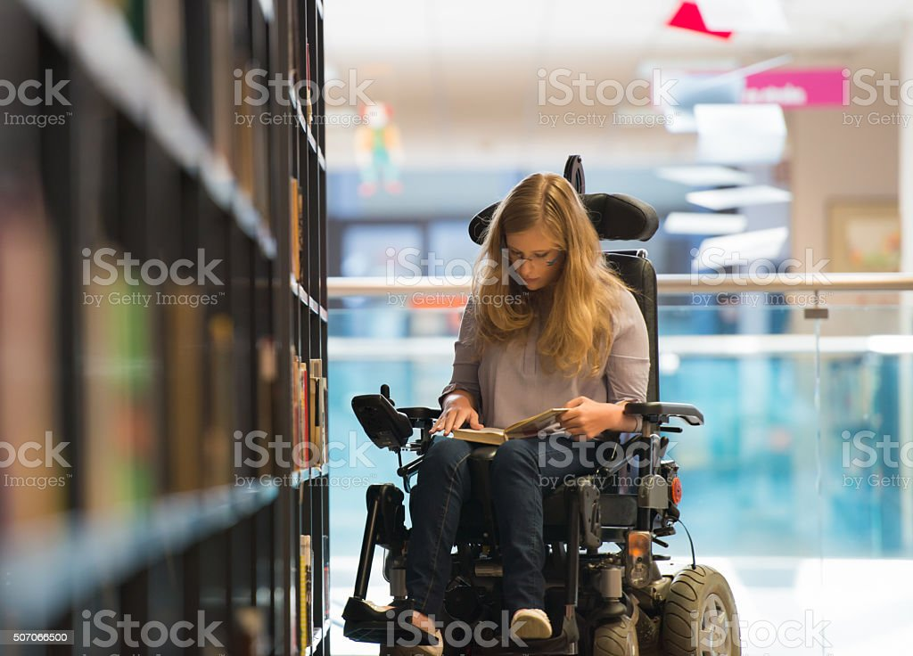 Niña en la biblioteca para personas con discapacidades - foto de stock