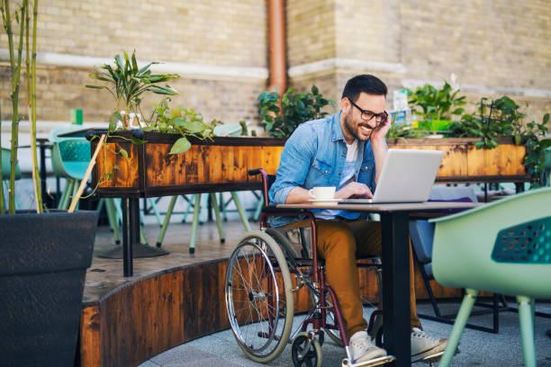hombre con discapacidad en el café - wheelchair fotografías e imágenes de stock