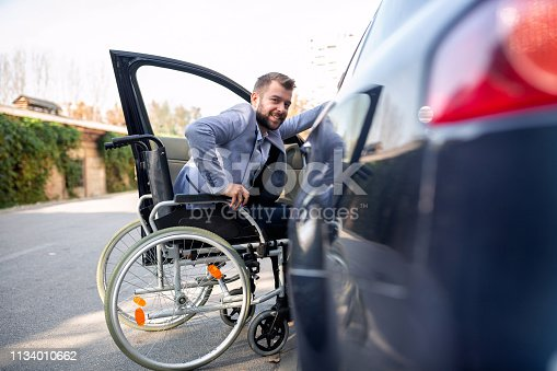 istock Handicapped man attempting to get in the car 1134010662
