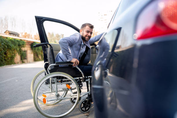 Handicapped man attempting to get in the car stock photo