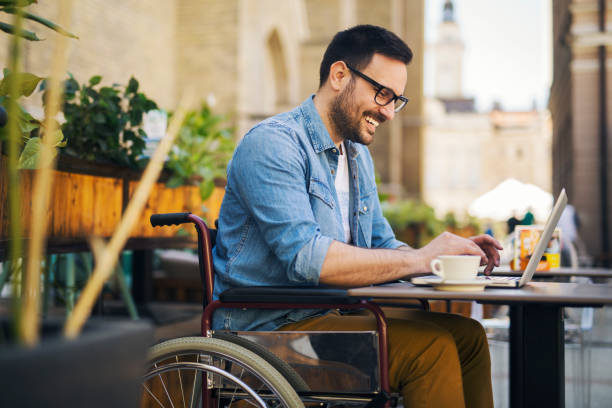 Handicapped man Handsome young handicapped man in wheelchair sitting in cafe and working on laptop persons with disabilities stock pictures, royalty-free photos & images