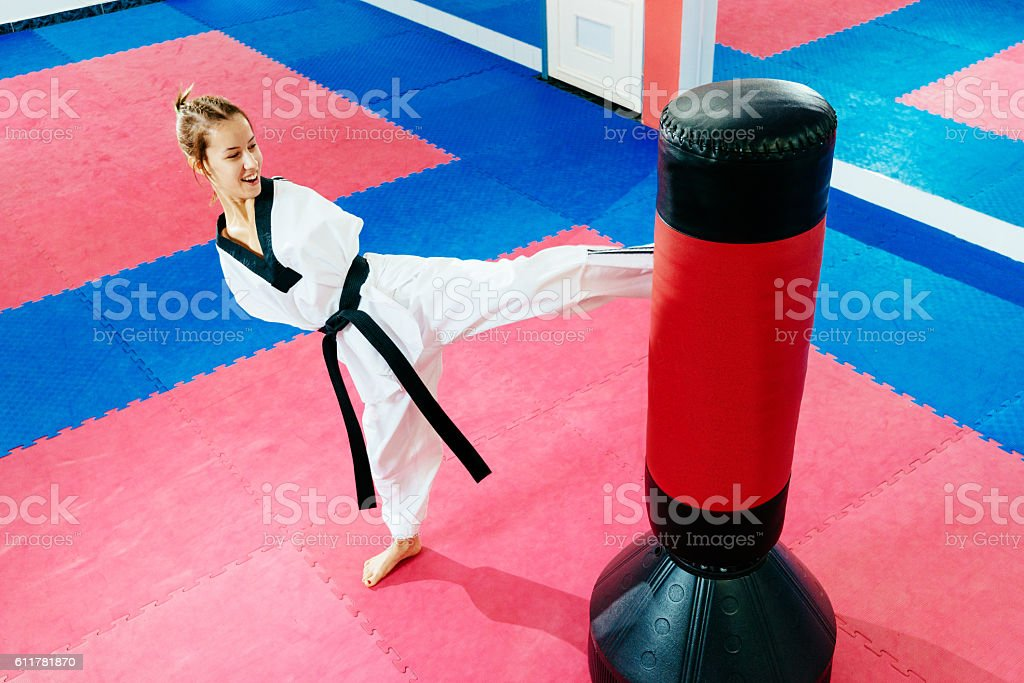 Handicapped martial arts trainee kicks punching bag stock photo
