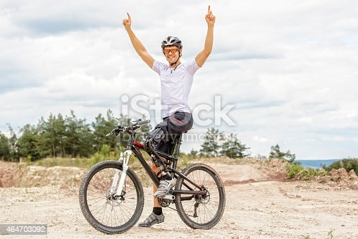 istock Handicapped mountain bike raising up arms 464703092