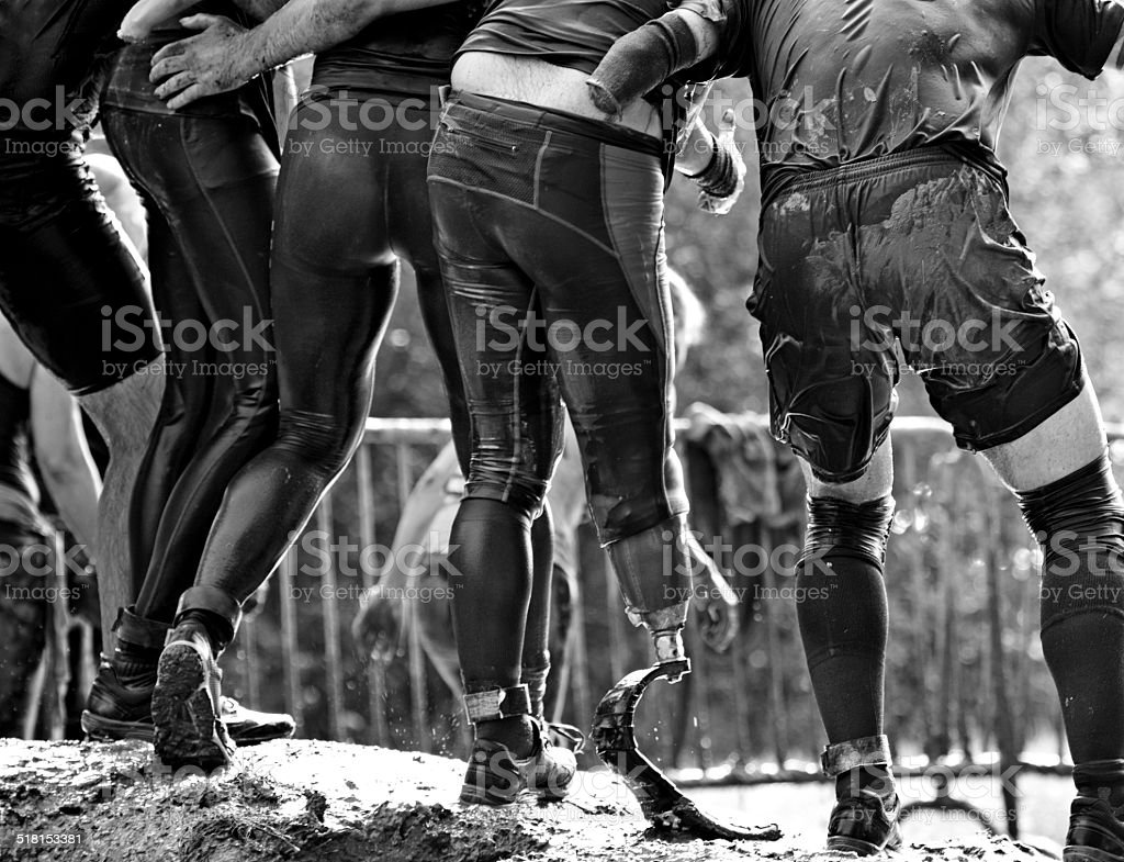 handicapped runners during the mud obstacle run stock photo