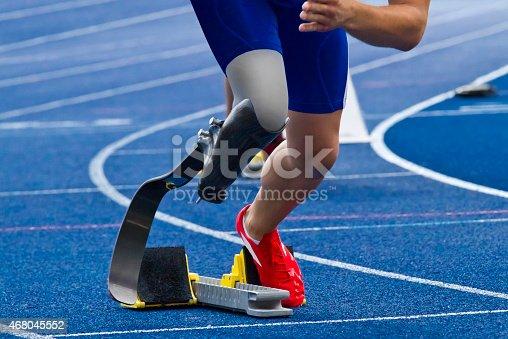 istock Handicapped sprinter on blue track 468045552
