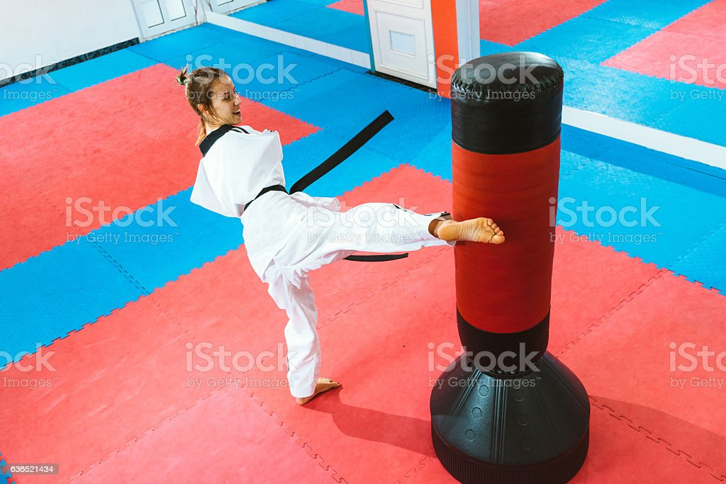 Handicapped taekwondo girl kicking right round kick stock photo