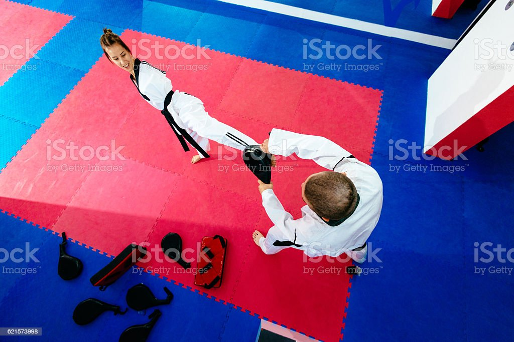 Handicapped taekwondo trainee kicks focus pads stock photo