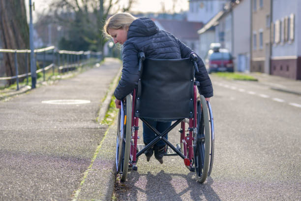 Handicapped woman using her wheelchair in a street stock photo
