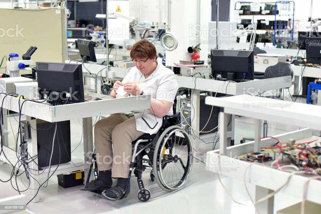 Behinderte Arbeitnehmer in einem Rollstuhl, Montage von elektronischen Komponenten in einer modernen Fabrik am Arbeitsplatz – Foto
