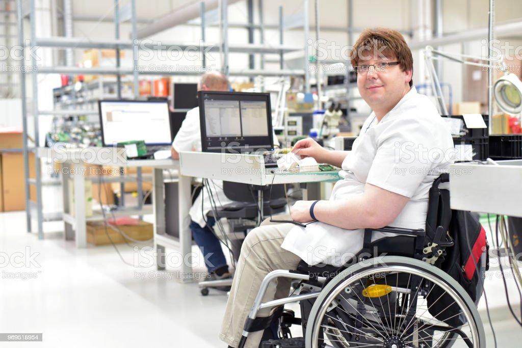 trabajadores con discapacidad en silla de ruedas, montaje de componentes electrónicos en una moderna fábrica en el lugar de trabajo - foto de stock