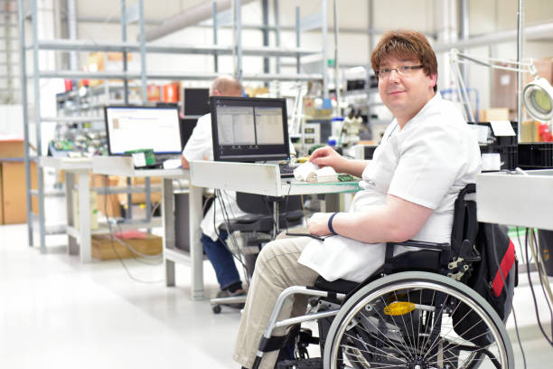 handicapped worker in a wheelchair assembling electronic components in a modern factory at the workplace - handicapped imagens e fotografias de stock