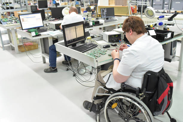 handicapped worker in a wheelchair at a workplace in a electronics manufacturing and assembly factory stock photo