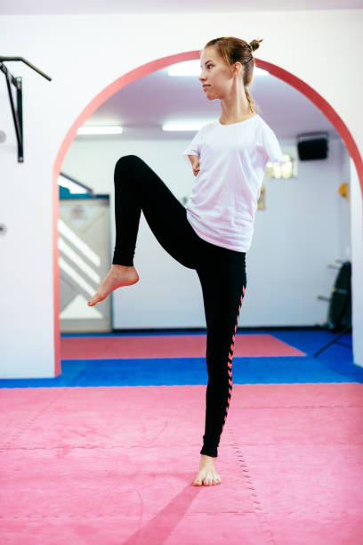 Handicapped young woman exercising taekwondo - female amputee on martial arts training stock photo