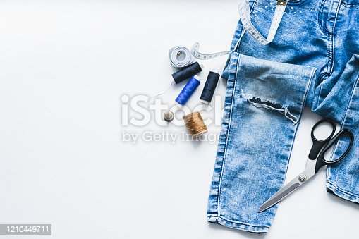 istock Handicraft, clothing repair. Ripped blue jeans sewing accessories white background. The concept of economical things. 1210449711