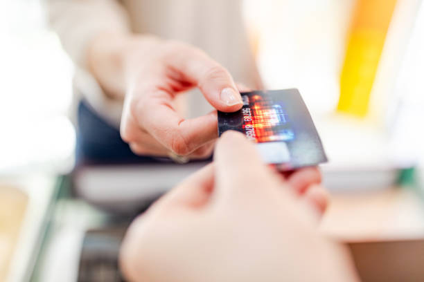 Handing credit card to cashier Close-up of handing credit card to cashier. Note to inspector: Design elements is design by us, name and credit number is generic credit card purchase stock pictures, royalty-free photos & images