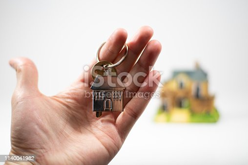 Hand holding a keychain with a key for the house shown in the background