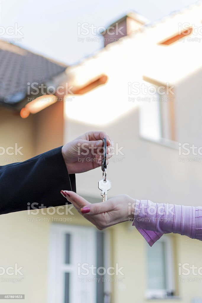 Handing  keys in front of house royalty-free stock photo
