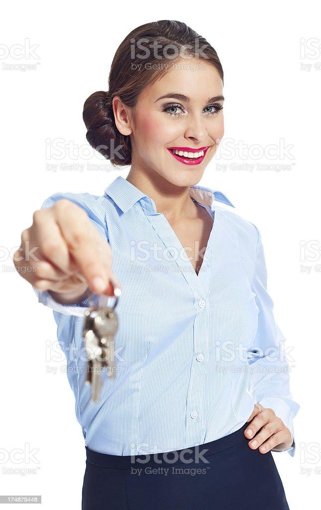Handing keys Portrait of female real estate agent standing against white background and handing keys. 20-24 Years Stock Photo