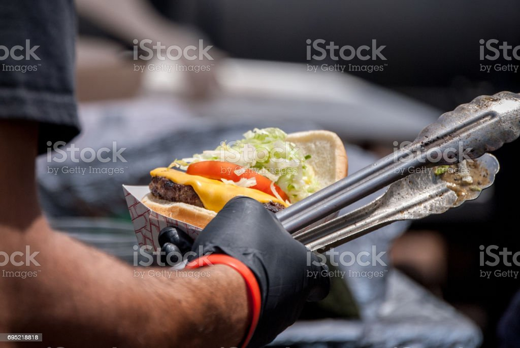 Handing over a finished hamburger stock photo