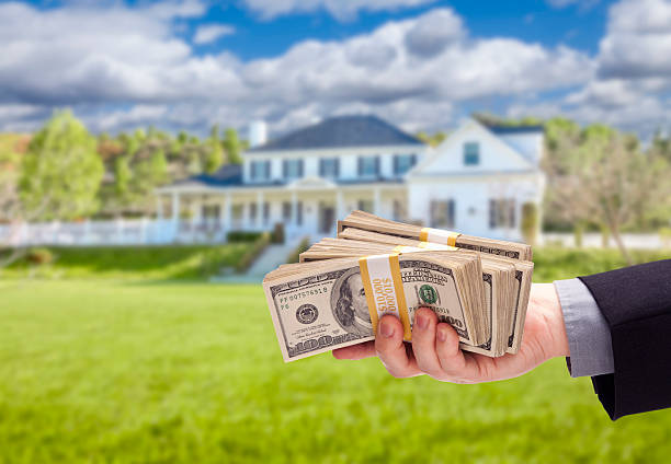 Handing Over Cash For House in Front of Home stock photo