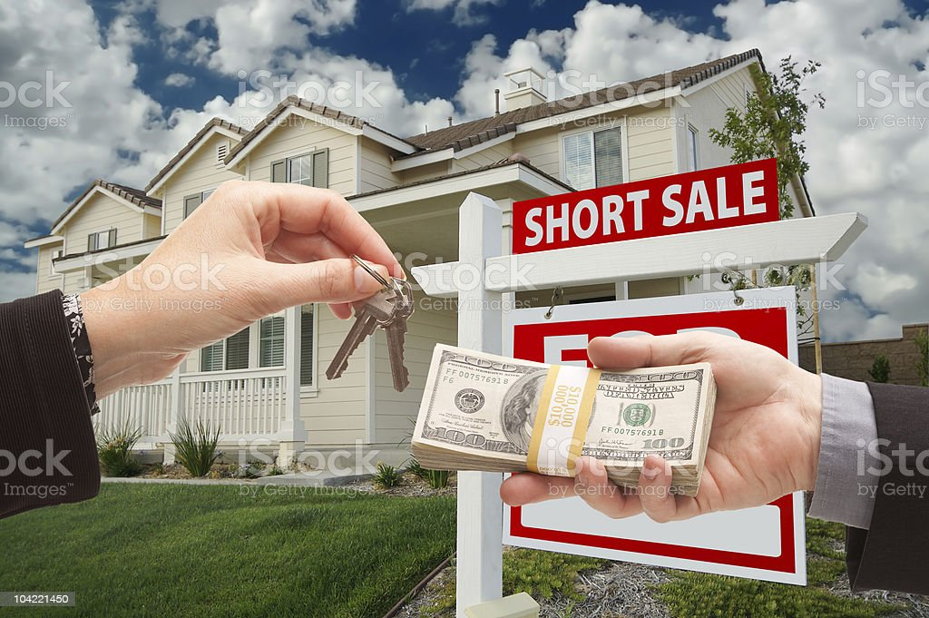 Handing Over Cash For House Keys and Short Sale Sign stock photo