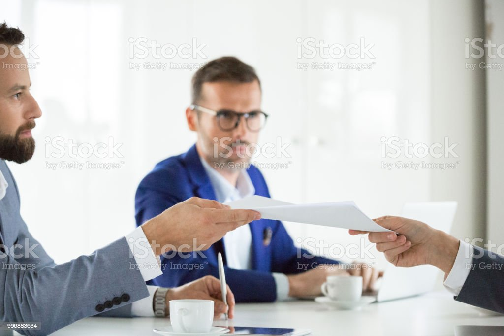 Handing over contract documents Businessman handing over a document to colleague in meeting. Business people working over new contract in meeting. Adult Stock Photo
