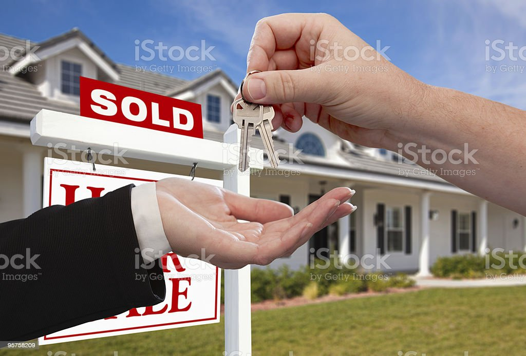 Handing over house keys in front of sold sign stock photo