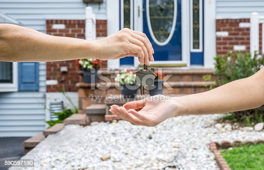 istock Handing Over the Key from a New Home 590597190