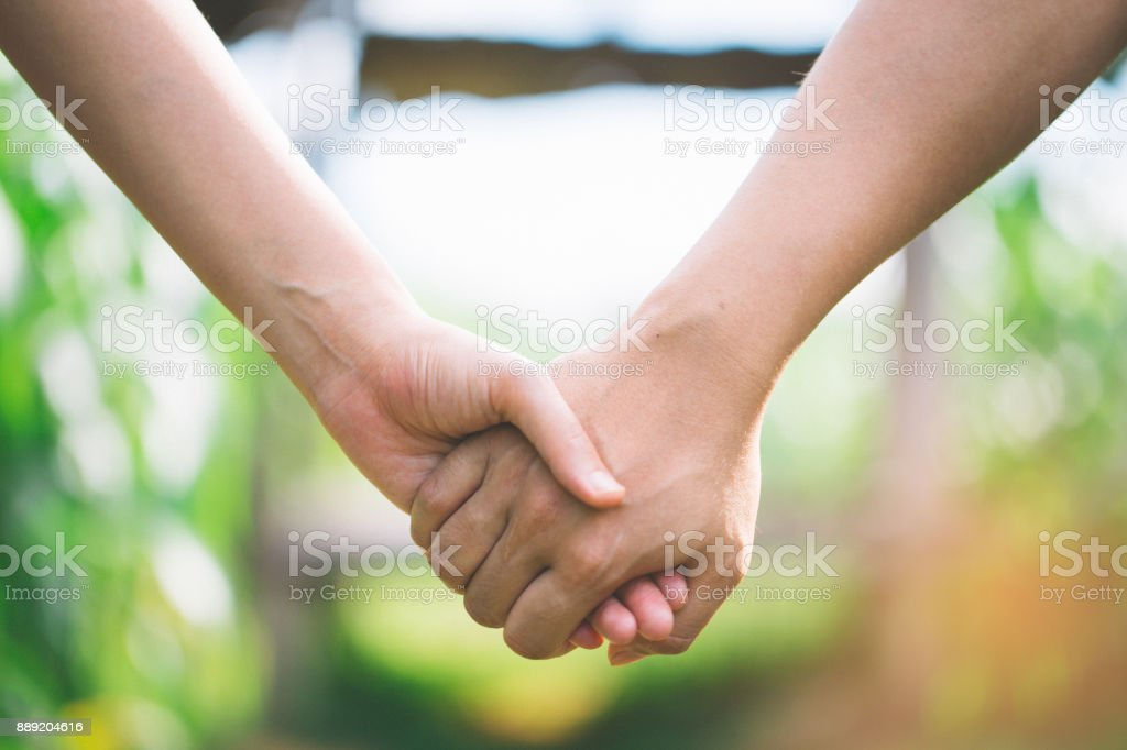 Hand-in-hand. Couple love in forest. stock photo