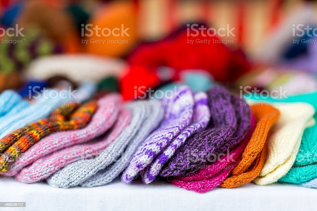Hand-knitted multicolored baby socks lined up in a row stock photo