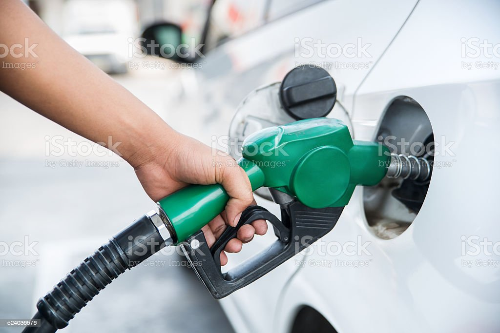 Handle fuel nozzle to refuel the car. - Royalty-free Adult Stock Photo