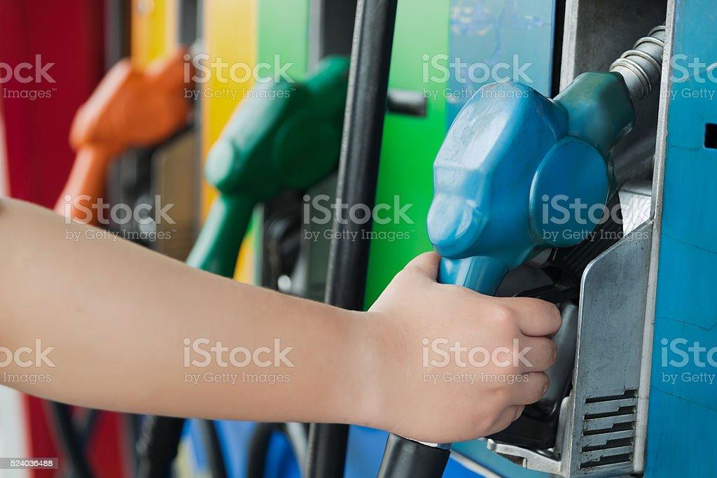 Handle gasoline dispensing facilities fueling vehicles. stock photo