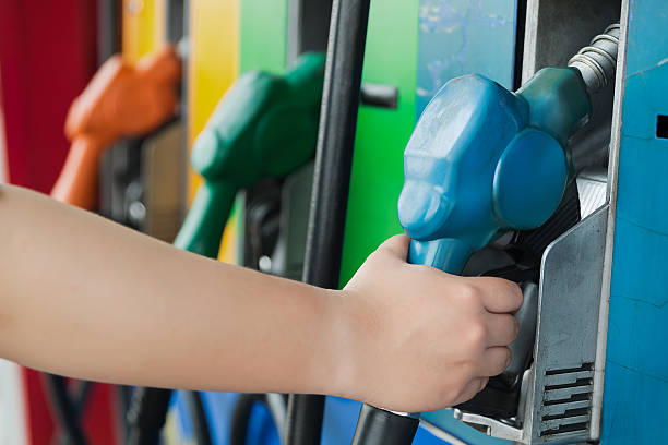 Handle gasoline dispensing facilities fueling vehicles. stock photo
