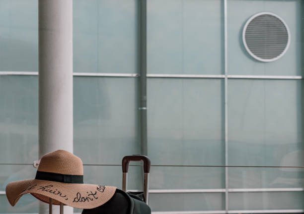 Handle of suitcase with fancy straw hat at airport of Paris stock photo
